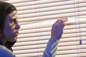 Woman Looking Out Window Through Blinds